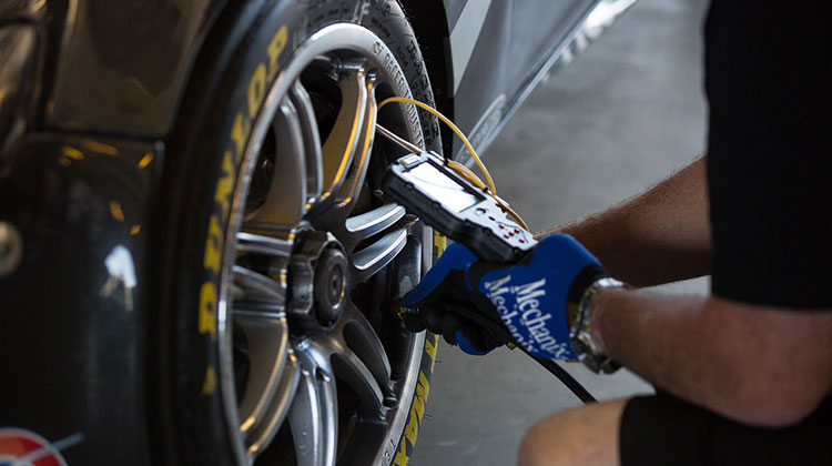 V8 Supercars technical staff carry out tyre pressure checks